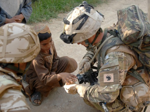 "Image shows: Lance Corporal Michael McLoughlin cleaning a cut on a local boy's hand with the water from his camelbak drinking system.  Lance Corporal (LCpl) Michael ""Doc"" McLoughlin is a medic with the Royal Army Medical Corps attached to The Royal Dragoon Guards. He is currently serving with a ground holding unit on the frontline against the Taliban in the southern district of Nad-e-Ali. The patrol base was seized as part of operation Moshtarak early in the year.    LCpl McLoughlin (22) from Manchester is the first line of medical support for the soldiers of C Squadron Royal Dragoon Guards who are currently operating as an infantry unit for their six-month tour of Afghanistan. The patrol base is some two kilometres from other ISAF locations. It regularly comes under fire from insurgents, as do the soldiers who patrol the surrounding area to provide protection and security for the local villagers."
